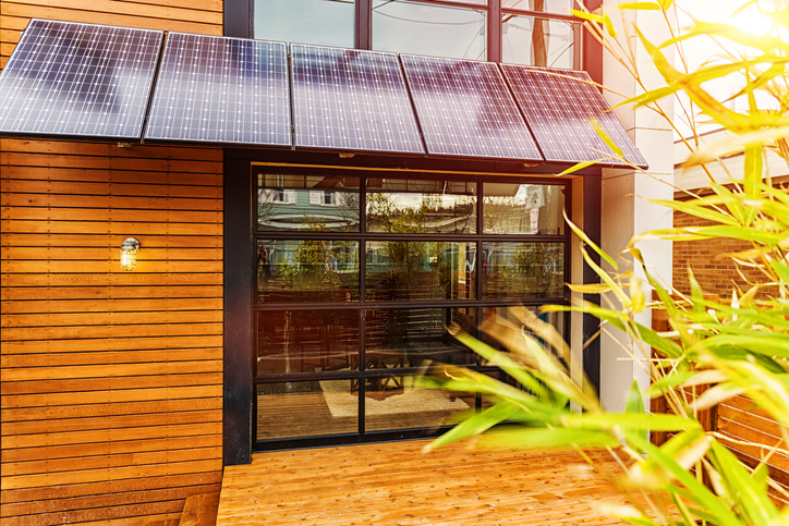 Photo of a modern home exterior with a solar power awning over the back porch